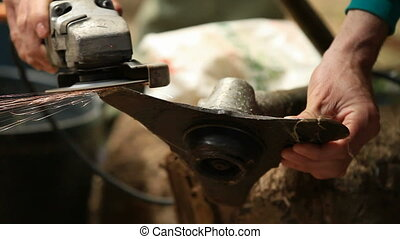 sharpening - A working man using an electric grinder for...