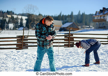 Guy and girl play snowballs.