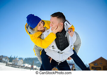 Young man holding his girlfriend on his shoulders