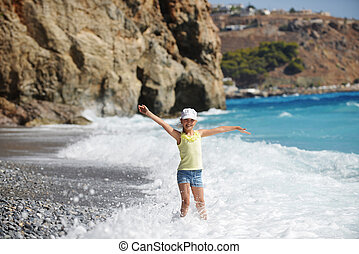 cute  girl playing on shore of blue sea