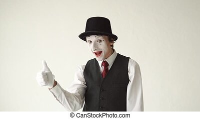 man mime shows thumbs up over white background.
