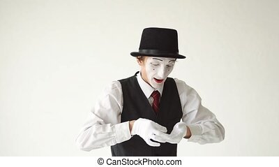 cheerful mime standing on a white background and counts the money