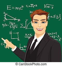 young male math teacher with piece of chalk standing next to blackboard