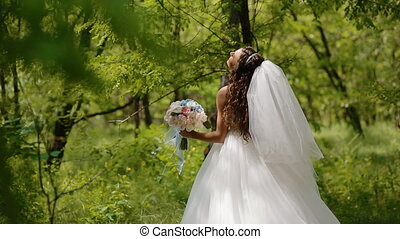 Beautiful bride pose with wedding bouquet outdoor in sunny...
