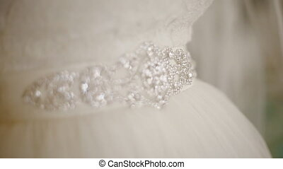 Putting a belt decorated with beads - Bride putting a belt...