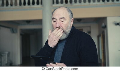 Old man shocked and happy of looking on tablet in 4K.