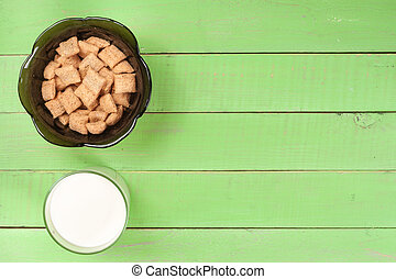 glass of milk with grain crispbreads on a green wooden background with copy space for your text. Top view