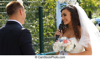 Bride says the oath at wedding ceremony standing in arch...