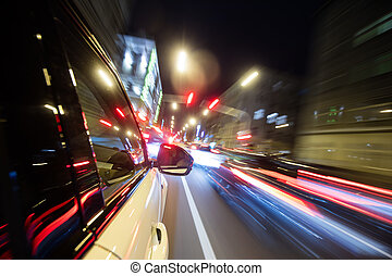 Car driving in city at night, blur motion