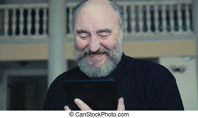 Emotional happy old man chatting on the tablet