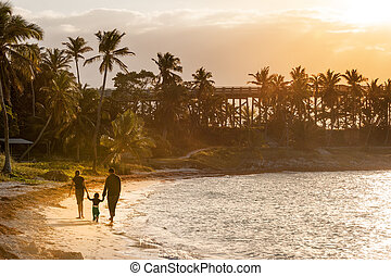 Sunset on paradise island - Family strolling on sandy beach...