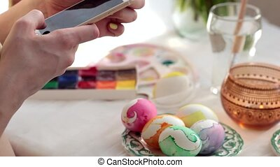 Easter, holidays, tradition, technology and people concept - close up of woman hands with smartphone taking picture of colored easter eggs