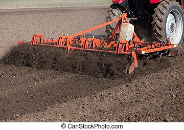 Tractor harrowing soil in spring - Tractor harrowing soil in...
