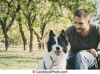 Man with his dog playing outdoor in the park. Young owner...