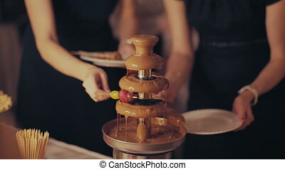 chocolate fountain, the chocolate is poured on the fruit.
