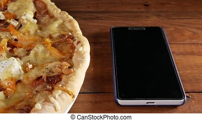 The mobile phone rests on a wooden table next to a homemade pizza with different cheeses and tomato. Moving camera