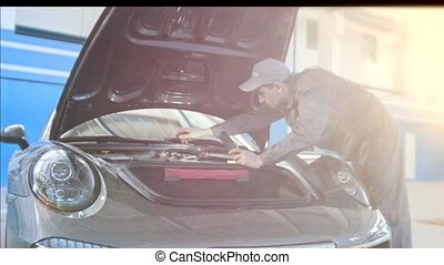 Mechanic working in the garage - repairing luxury sportcar