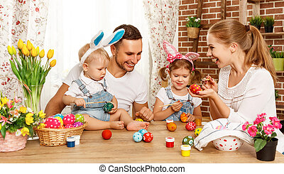 Happy easter! family mother, father and children paint  eggs for holiday