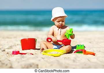 baby boy playing with toys and sand on beach