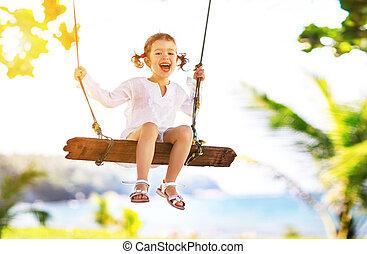 Happy child girl swinging on swing at beach in summer -...