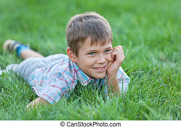 Handsome boy on the green grass - A portrait of a handsome...