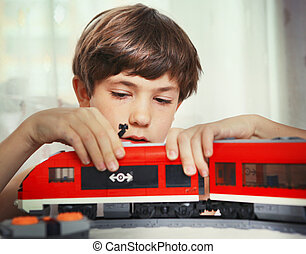 preteen handsome boy play with meccano toy train and railway...