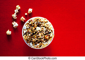 Sweet Bowl with popcorn on a red background, cinema, movies and entertainment concept
