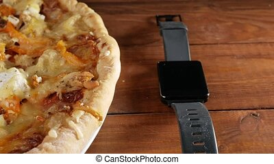 Smart watches lie on a wooden table next to a homemade pizza with different cheeses and tomato. Moving camera