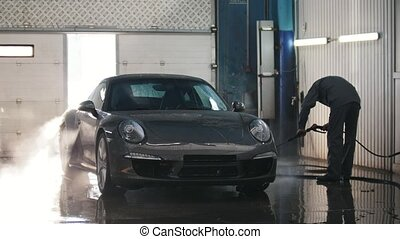 Worker in car service is washing a luxury sport car in the suds by water hoses