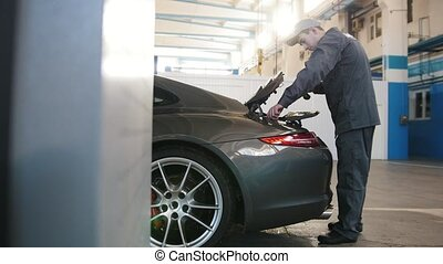 Mechanic in car workshop - checking and repairing...