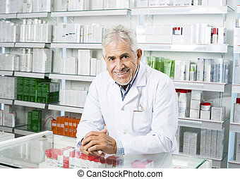 Chemist Standing With Hands Clasped At Counter - Portrait of...