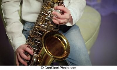 The boy plays the saxophone - The Musician Playing the...