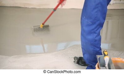 Dirt the floor with a roller - The builder smooths the...