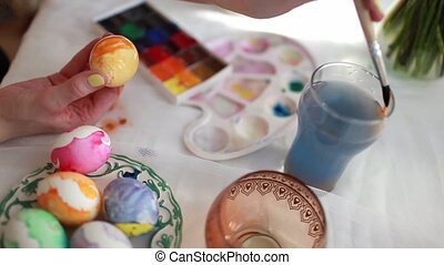 Redhead girl paints Easter eggs with a brush. on the table Easter cake, eggs, sweets, bouquet of flowers.