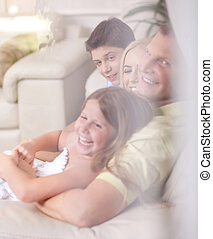 Happy family smiling and looking  behind the window glass