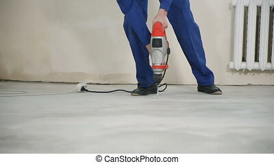 The worker drills the floor - The worker drills the hole in...