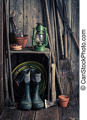 An old rustic shed with garden tools and clay pots