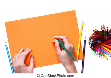 Human hands with pencil drawing something on the orange paper isolated on white background
