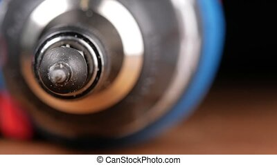 The screw is wearing a bit of electric screwdriver. Macro photography moving camera