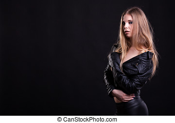 Woman with no bra in leather jacket on black background in...