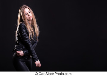 Hot woman with no bra in leather jacket on black background...