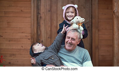 Boy sitting on grandfather knees, girl standing behind and hug. Brother and sister playing with toy sheep, laughing. 4K