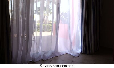 Swinging curtain on the wind in hotel resort room with...