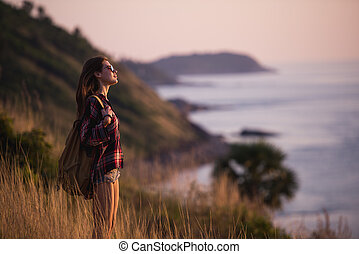Summer sunny lifestyle fashion portrait of young stylish hipster woman walking in mountains, wearing cute trendy outfit, smiling enjoy weekends, travel with backpack. Awesome ocean view on a background.