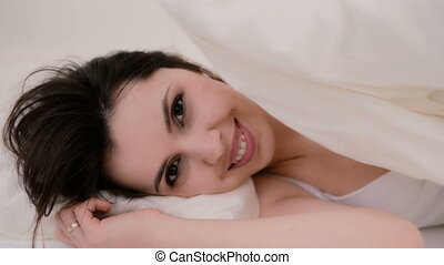 Fresh and happy brunette woman in bed at home. Beautiful girl hides under a blanket and smiling.