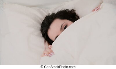 Close-up of a young beautiful woman with a funny look hiding under the blanket. Girl having fun in bed.