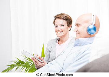 Relaxed contented middle-aged couple sitting side by side on...