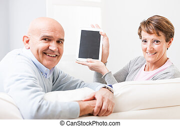 Attractive friendly middle-aged couple turning on a sofa and...