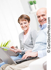 Happy couple relaxing with a laptop and tablet on a sofa at...