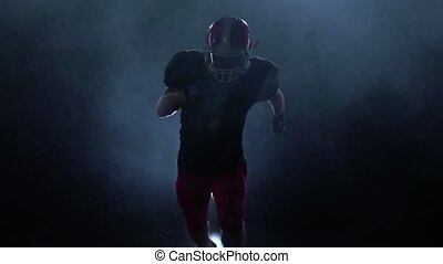 Forward player in american football attack. Slow motion. Isolated studio
